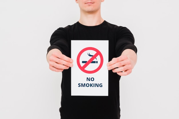 Man holding paper with no smoking text and sign on white wall Free Photo