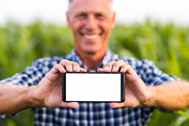 Man holding phone with both hands mock-up Free Photo