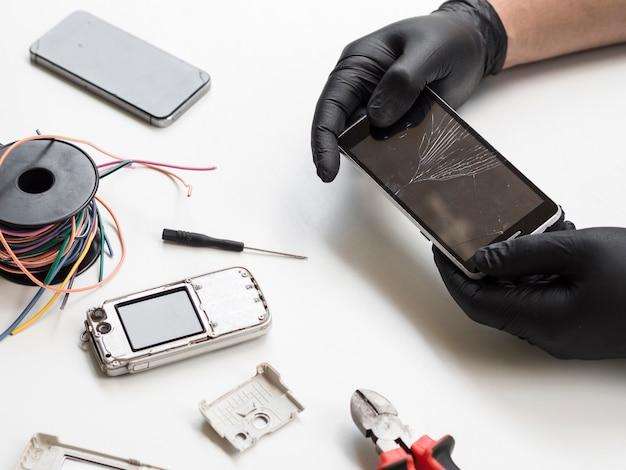 Мужчина держит телефон с разбитым дисплеем Premium Фотографии
