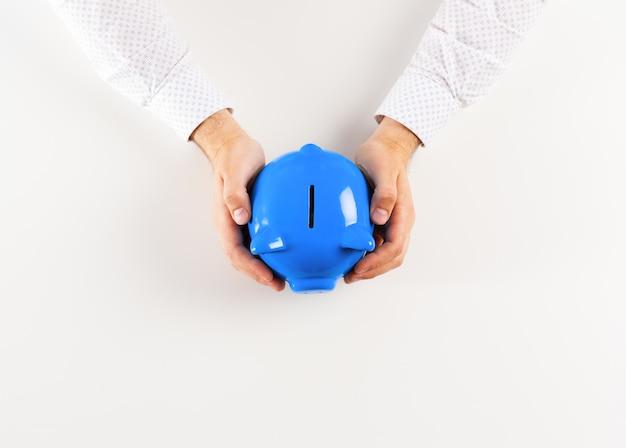 Man holding piggy bank . top view Premium Photo