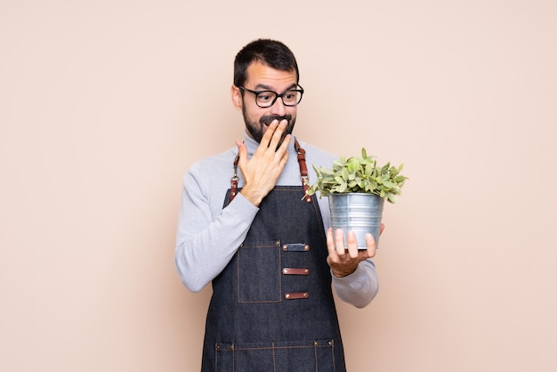 Man holding a plant over isolated  with glasses and surprised Premium Photo