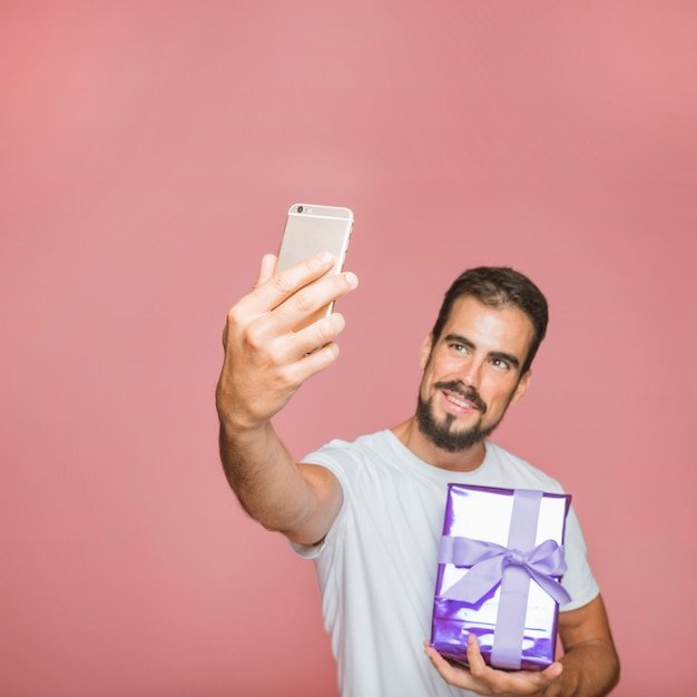 Man holding present taking selfie against pink background Free Photo