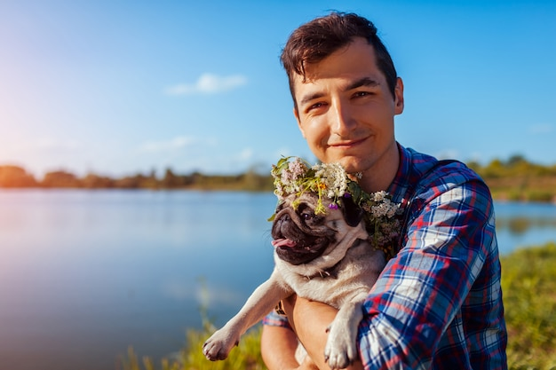 Man holding pug dog with flower wreath on head. man walking with pet by summer lake Premium Photo