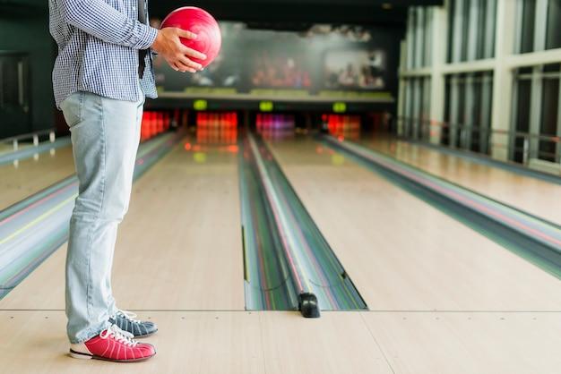 Uomo che tiene una palla da bowling rossa Foto Gratuite
