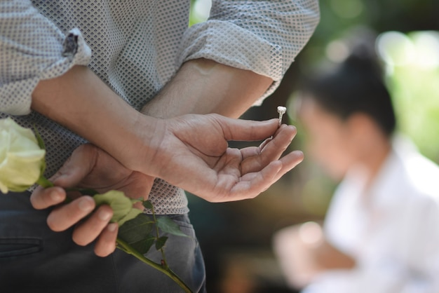 A man holding a ring and rose behind him about to give and propose to a woman Premium Photo