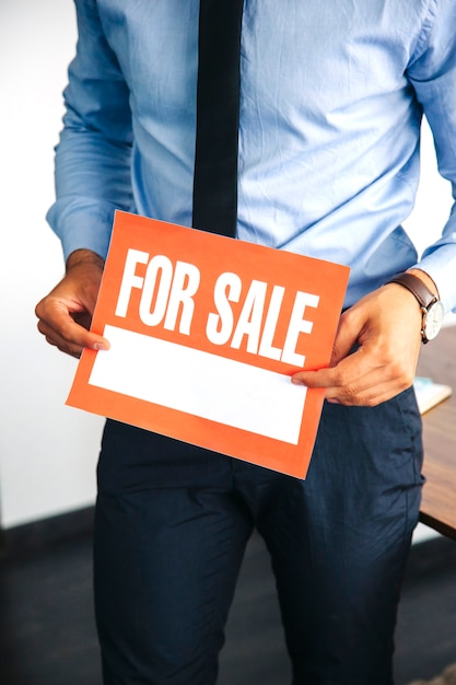 Man holding for sale sign Free Photo