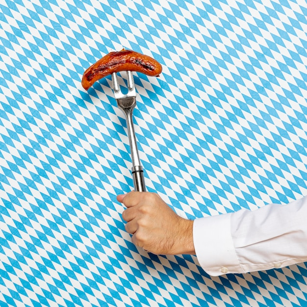Man holding sausage with patterned background Free Photo