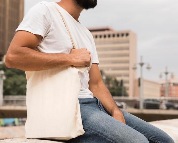 Человек, держащий хозяйственную сумку в городе Бесплатные Фотографии