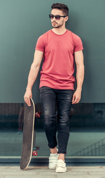 Man holding a skate in his hand. Premium Photo