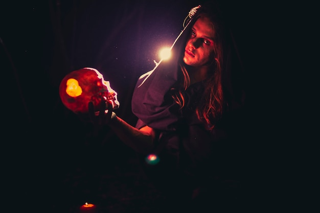 Man holding a skull in the dark and looking at camera Free Photo