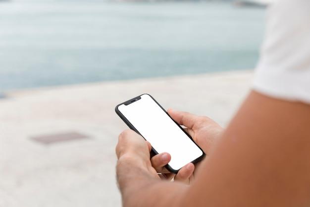 Мужчина держит смартфон на открытом воздухе с копией пространства Бесплатные Фотографии