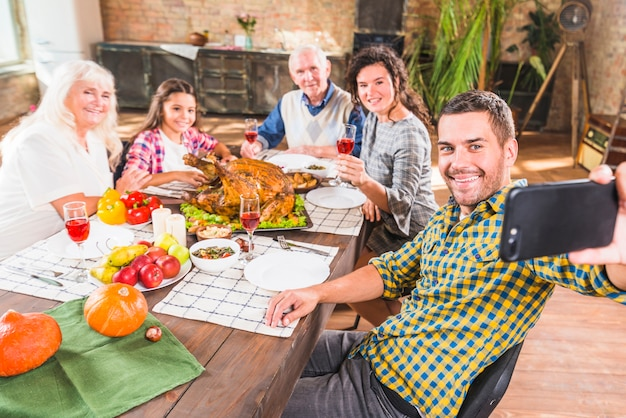 Man holding smartphone at table with family Free Photo
