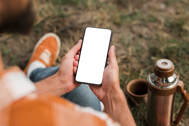 Man holding smartphone while camping outdoors Free Photo