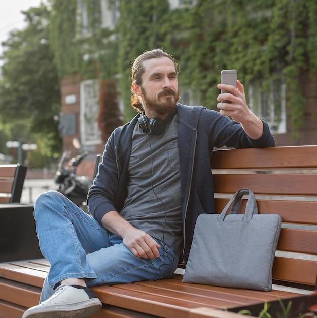 Мужчина держит смартфон с сумкой для ноутбука в городе Бесплатные Фотографии