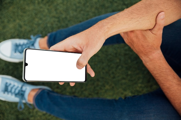 Man holding smartphone with mock-up Free Photo