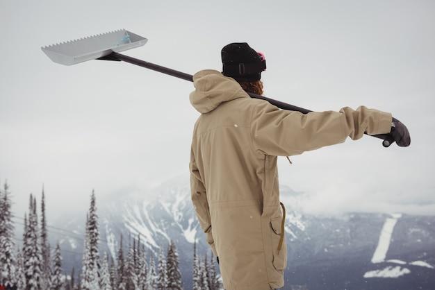 Uomo che tiene la pala da neve nella località sciistica Foto Gratuite