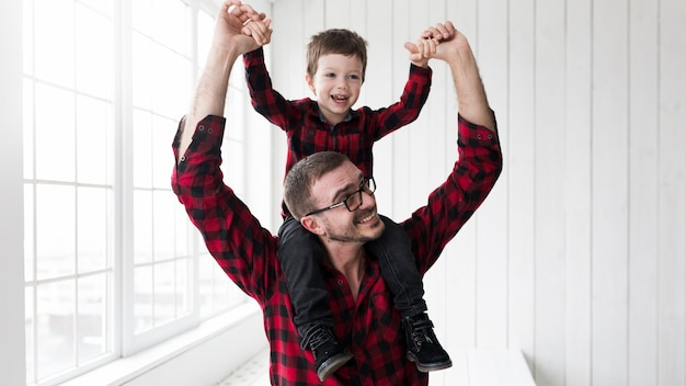 Man holding son on fathers day in front of chalkboard Free Photo