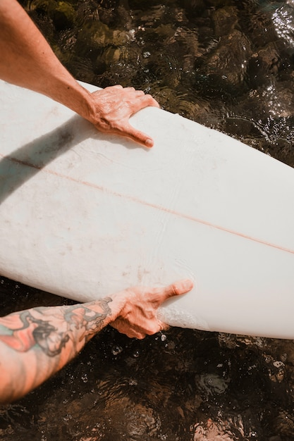 Man holding surf board on water Free Photo