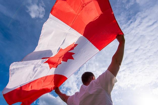 青い空を背景にカナダの国旗を保持している男 Premium写真