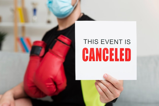 Man holding a this event is canceled card Free Photo