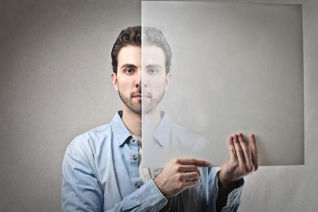 Man holding a transparent sheet in front of his face Premium Photo
