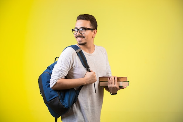 Uomo che tiene due libri e sorridente. Foto Gratuite