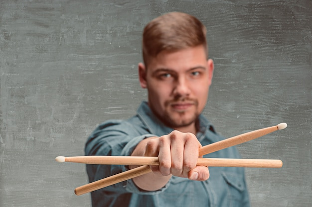 Man holding two drumsticks over gray wall Free Photo