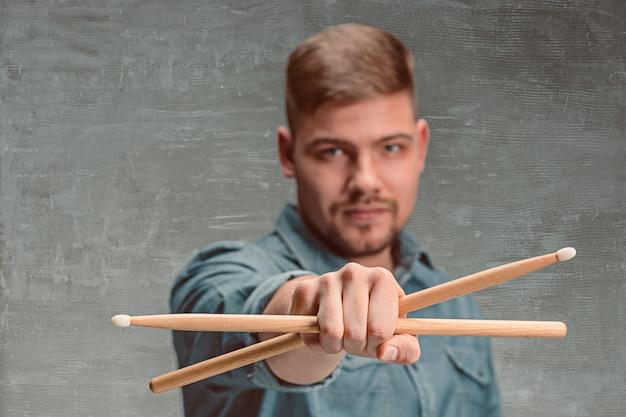 Мужчина держит две барабанные палочки над серой стеной Бесплатные Фотографии