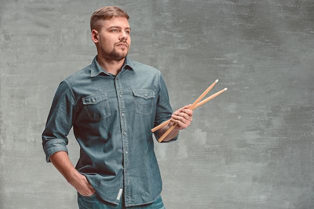 Мужчина держит две барабанные палочки над серым Бесплатные Фотографии
