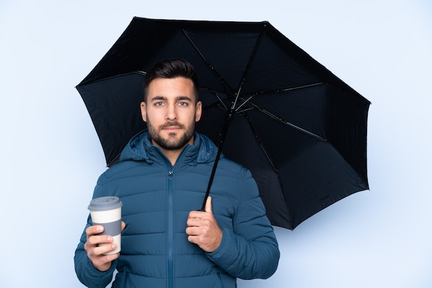 Man holding an umbrella over isolated wall Premium Photo