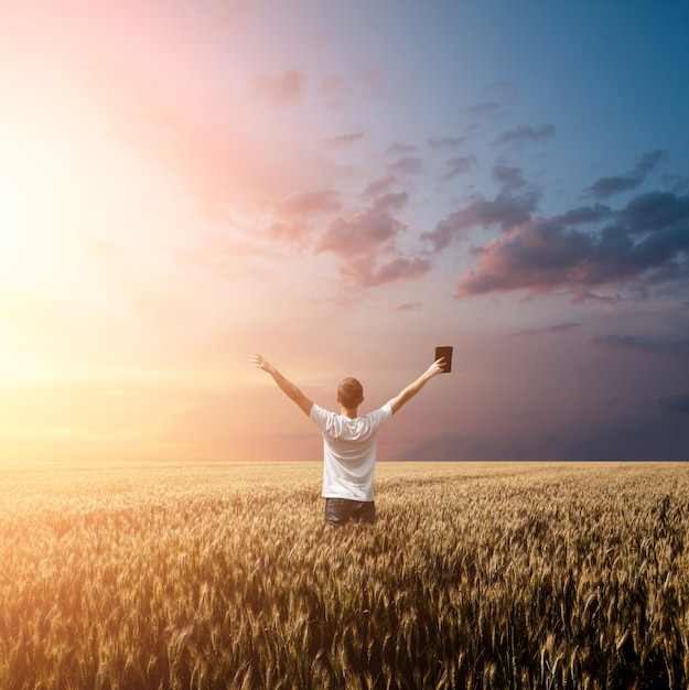 Man holding up bible in a wheat field Premium Photo