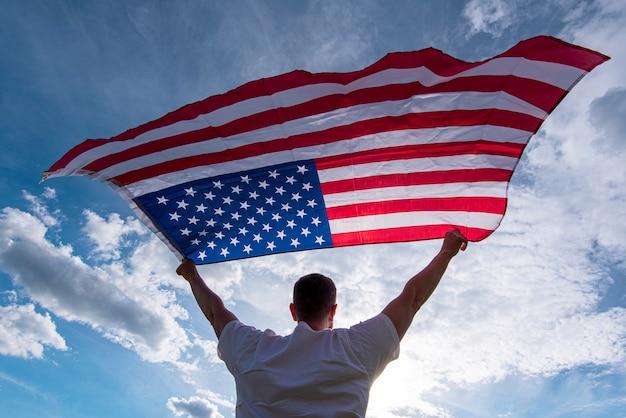 アメリカ、コンセプト画像の手でアメリカの旗を振って保持している男 Premium写真