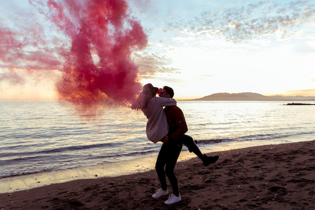 Man holding woman in arms with pink smoke bomb on sea shore Free Photo