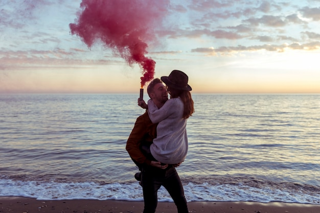 Man holding woman in arms with smoke bomb on sea shore Free Photo
