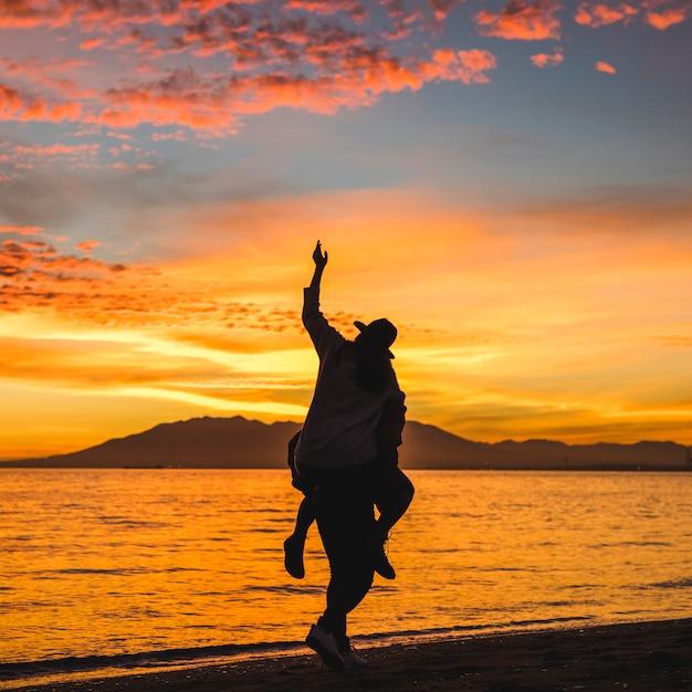 Man holding woman on back on dark sea shore Free Photo