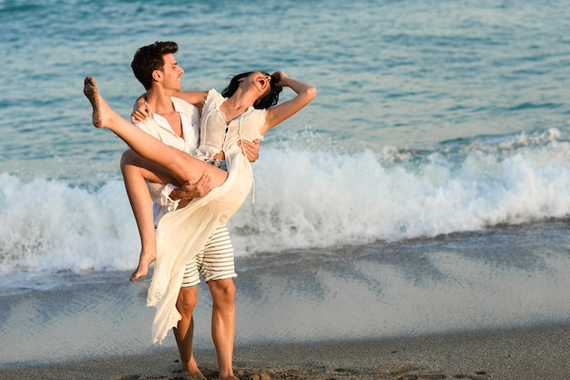 Man holding a woman in white dress on the beach Free Photo