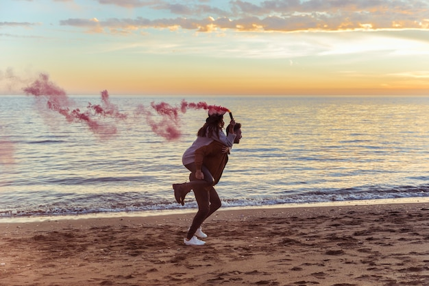 Man holding woman with pink smoke bomb on back Free Photo