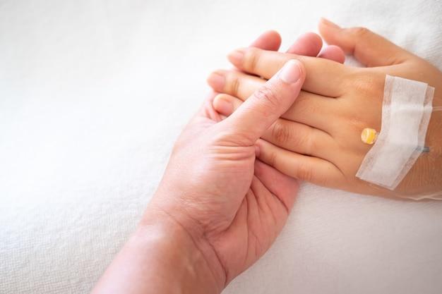 病院で女性の手を握って男。病院で病気の女性。医療コンセプトを持つ人々。 Premium写真