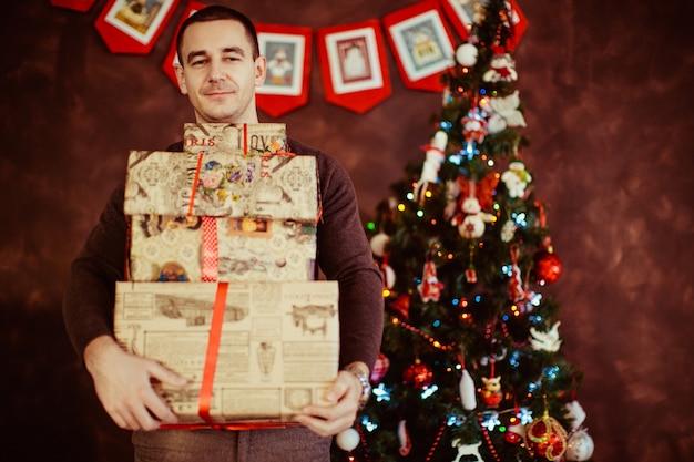 人はクリスマスツリーの近くでたくさんの贈り物をしています。 無料写真