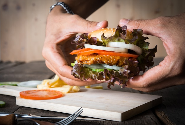 Man holds burger with hands potato chip 1150 1862