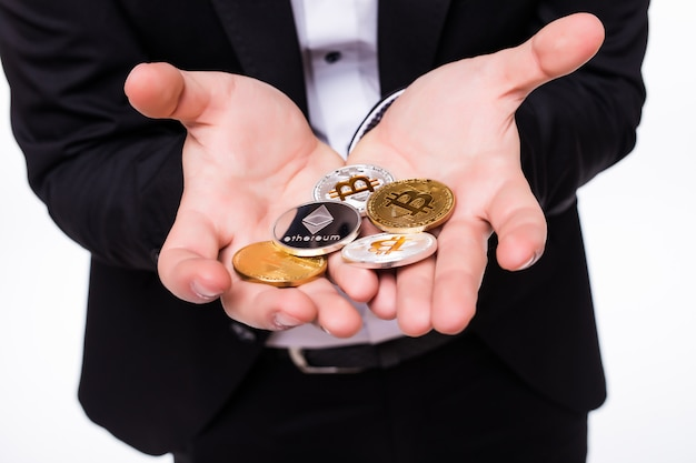 Man holds different crypto coins in his hands on white Free Photo
