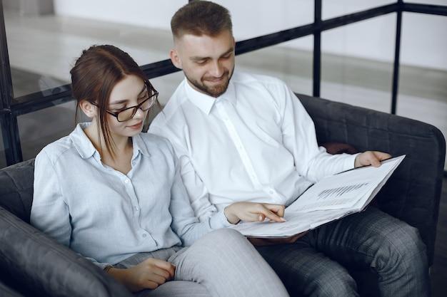 L'uomo tiene una cartella. partner commerciali in una riunione d'affari. donna con gli occhiali Foto Gratuite