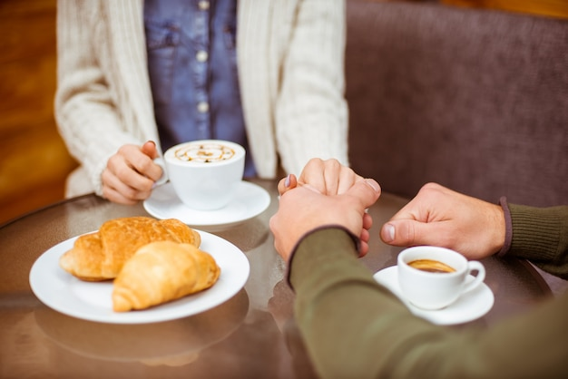 A man holds a girl's hand in a cafe. Premium Photo