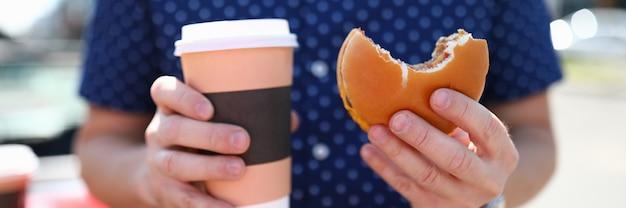 男は彼の手にホットコーヒーとハンバーガーとグラスを持っていますファーストフードの概念 Premium写真