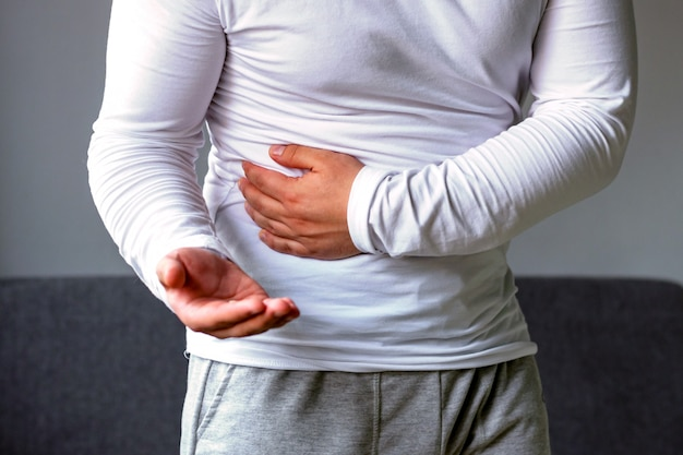 A man holds his stomach, stretches his hand with pills Premium Photo