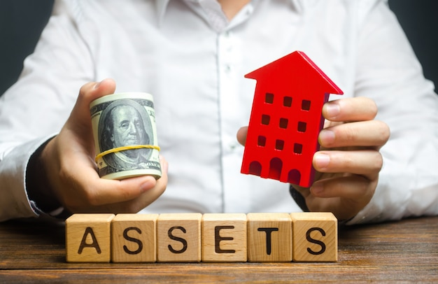 A man holds a red house and a roll of dollars over the word assets. declaration income and taxation Premium Photo