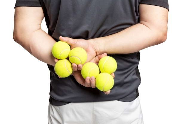 A man holds tennis balls in his hands. Premium Photo