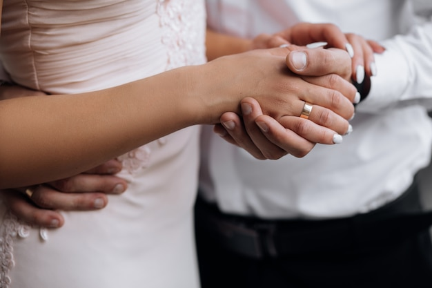 Man holds woman's hand tender in his strong arm Free Photo