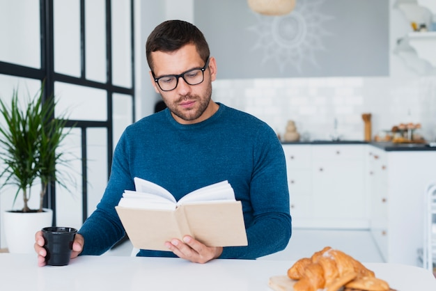 Man at home with glasses reading book Free Photo