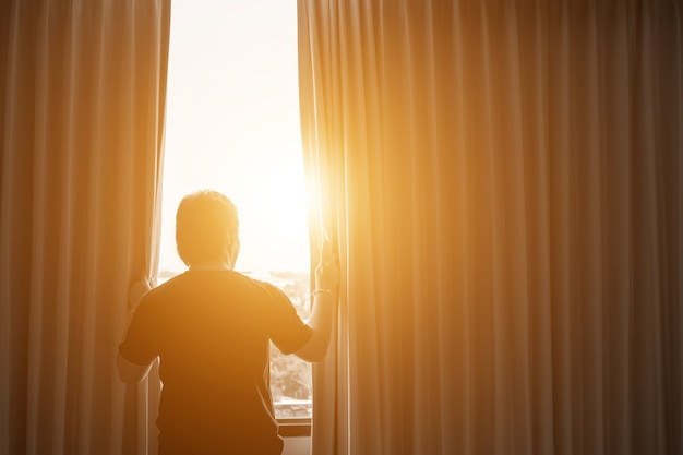 Man and hope concept . man opening window curtains Premium Photo